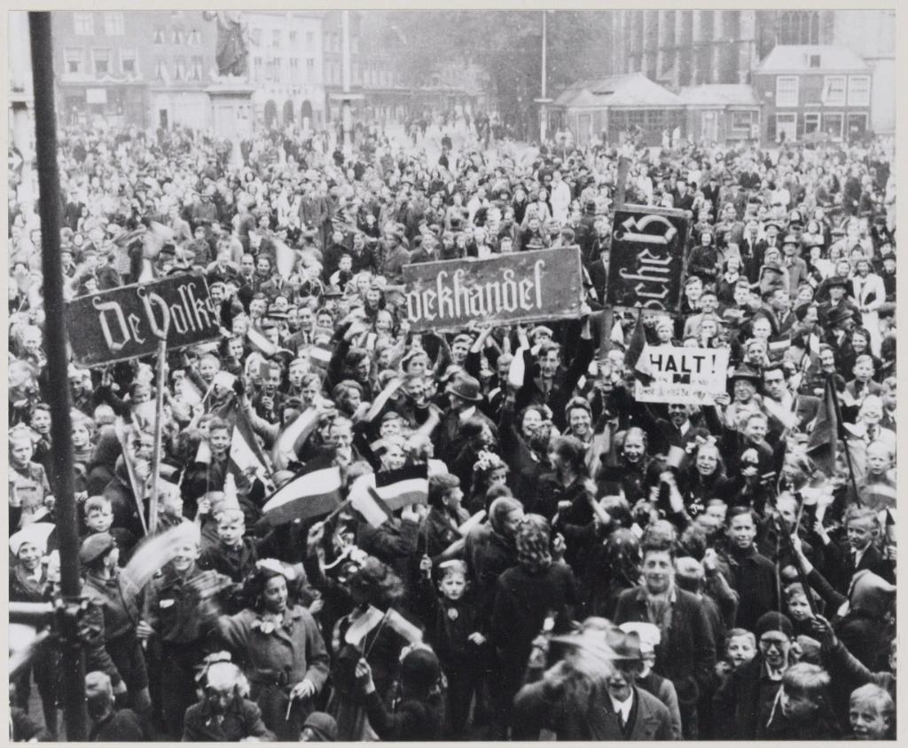 Duitse Bezetting, Verdediging 1940-1945 (Bevrijding) De bevrijding menigte op de Grote Markt, vermoedelijk op 5 mei. In de menigte staat tweede persoon rechts naast het bord met daarop HALT, Godfried Bomans. Noord Hollands Archief © BDU media