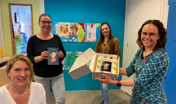Maike Douglas-Westland reikt eerste exemplaar De gelukkige leraar uit aan leerkrachten OBS Piet de Springer