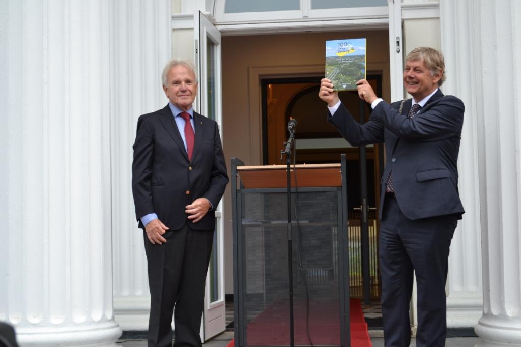 Burgemeester Roest is trots op het overhandigde boek uit handen van Wim Alferink (voorzitter 'Ons Bloemendaal'). Mariëlle Tukker © BDU Media