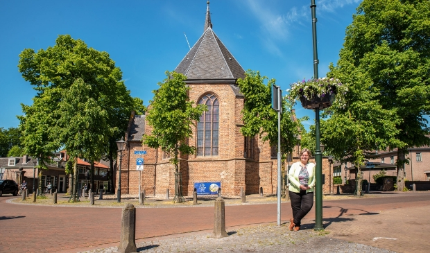 <p>Wethouder Henny van Dijk bij een van de onlangs opgehangen bloembakken in het dorpscentrum.</p>
