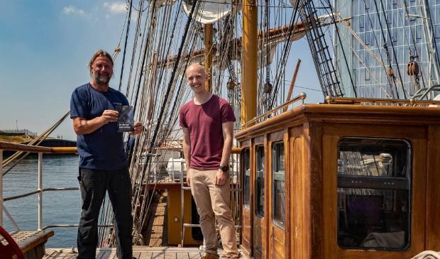 Kapitein Eric Kesteloo en schrijver Boris Lemereis op Bark Europa bij de overhandiging van het boek