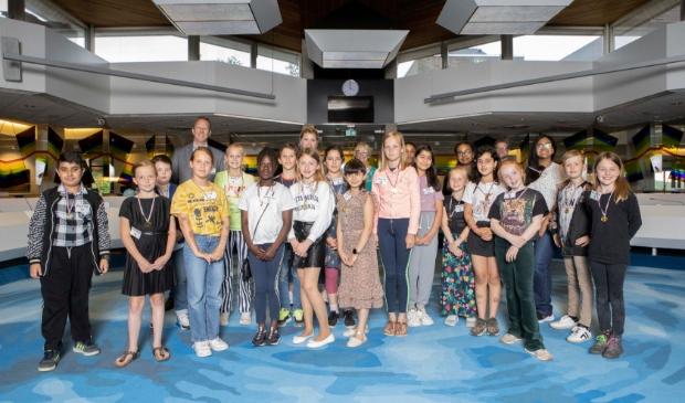 <p>De nieuwe kinderraad en kinderburgemeester gaan vol trots op de foto samen met de juryleden. Op de voorgrond in het midden, Bana met het donkere haar en bloemetjesjurk. </p>