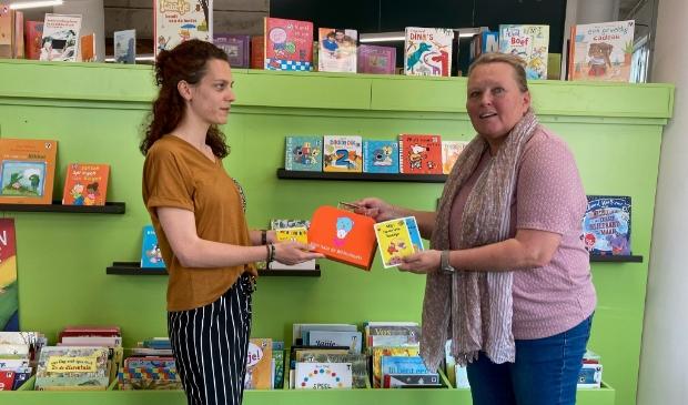 <p>Liesbeth Versteeg van de Bibliotheek Z-O-U-T reikt een BoekStartkoffertje uit en laat de baby- en dreumesboekjes zien.</p>