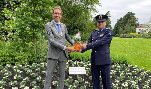 <p>Burgemeester Tjapko Poppens overhandigt veteraan Martijn Neumeier een pot met witte anjers..</p>