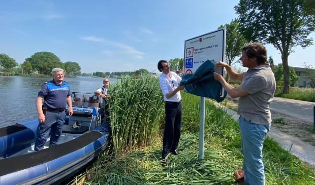 <p>Wethouder Herbert Raat onthult een bord met vaarregels die gelden op de Amstel in het bijzijn van Handhaving en Peter Hesp, voorzitter van de Vereniging Amstel Oever. </p>
