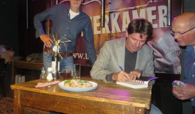 Twan Huys signeert zijn boek de Clintons in de Teerkamer.