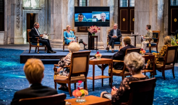 Gastsprekers vertellen over de historische en psychologische dimensies van de huidige coronapandemie. Op de voorgrond de koninklijke familie. Mely van Malenstein midden in het panel.