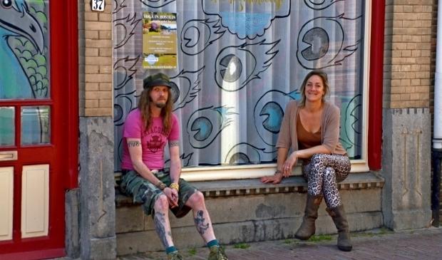 <p>De Wageningse kunstenaar Erwin Dijkhoff en Hanna Stellingwerf voor een door hen bewerkt etalageruit (foto Jan Boer)</p>