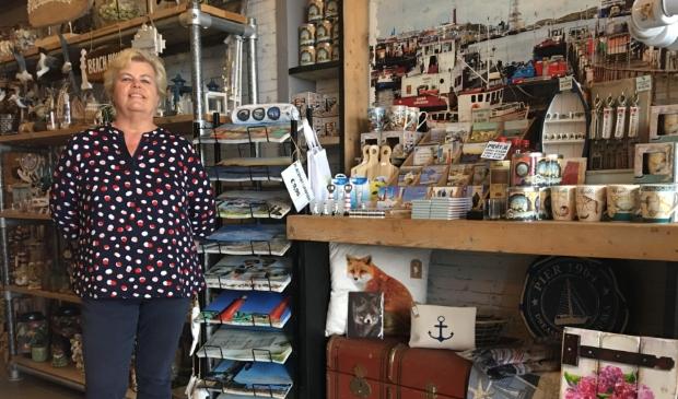 <p>Adrie Klinge in haar souvenirwinkel 'Groeten uit IJmuiden'.</p>