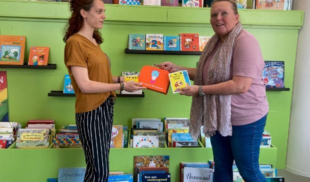 Liesbeth Versteeg van de Bibliotheek Z-O-U-T reikt een BoekStartkoffertje uit en laat de baby- en dreumesboekjes zien in de jeugdhoek van de Bibliotheek.