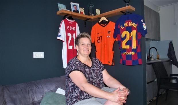 <p>Marjon Schuchhard met enkele prominente shirts van haar zoon Frenkie, in zijn ouderlijk huis in Arkel.</p>