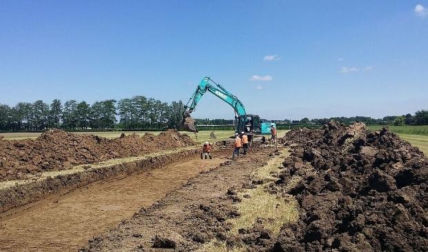 Het graven van een proefsleuf.