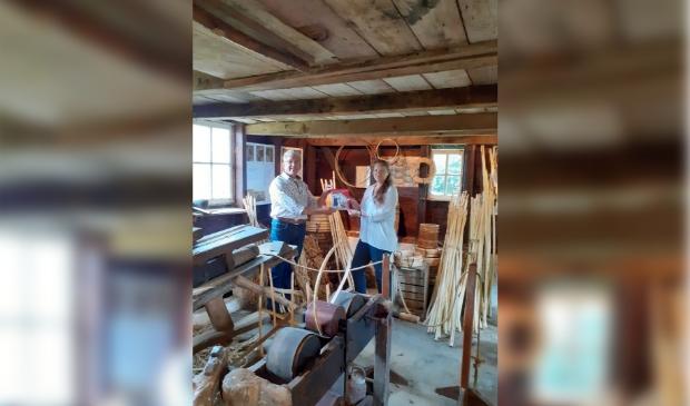 Schrijfster Ineke Kraijo overhandigt het boek Het geheim van de smid aan Hugo Vermeulen, medewerker van museum De koperen knop in de hoepmakersschuur