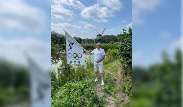 <p>Cees met zijn unieke Olympische vlag, liefst was hij op de atletiekbaan op de foto gegaan</p>