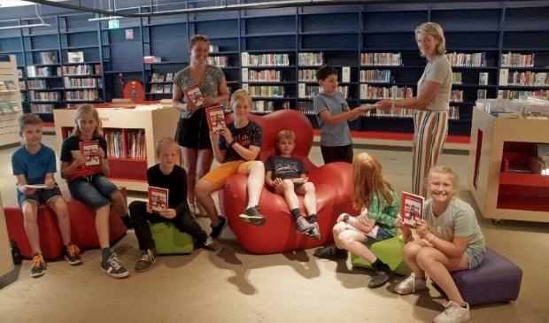 De schoolkrantredactie samen met Ivanka de Ruyter op bezoek bij José Tammer in de bibliotheek.