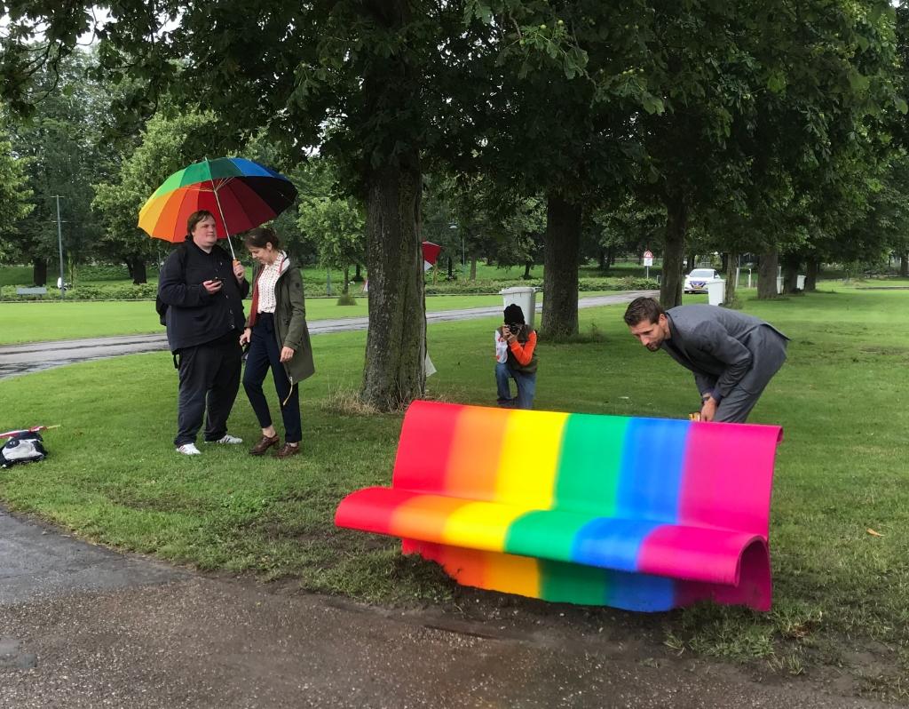 Wethouder Eelke Kraaijeveld schroeft het plaatje vast op het regenboogbankje, links onder de regenboogparaplu staat Maarten Venhoven Hannie Visser-Kieboom © BDU Media