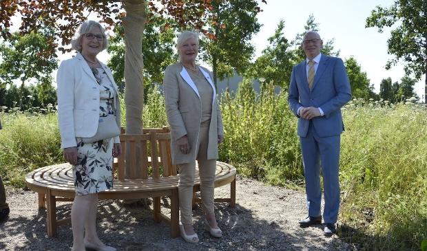 <p>Marianne Harterink, Hanne Vos en burgemeester Isabella bij het bankje onder de beuk</p>