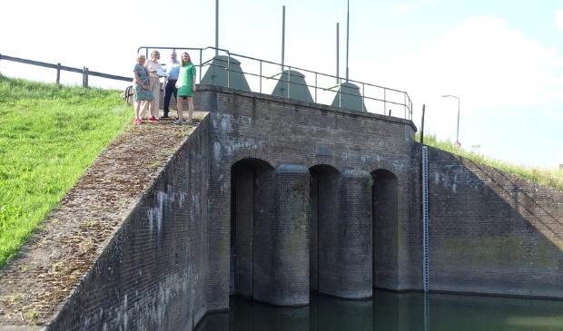 <p>Wil Kosterman (linksvoor) in 2019 bij de Inundatiesluis. Toen werden drie fietsroutes gepresenteerd langs de Nieuwe Hollandse Waterlinie. </p>