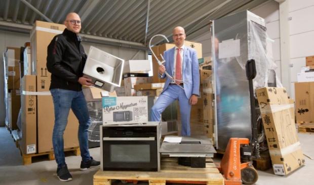 Eigenaar Johan van Velthuizen en keukendesigner Wilbrand Hardeman poseren tussen de onderdelen en apparaten.
