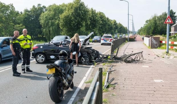 <p>De vrouw bekijkt de schade van de auto.</p>