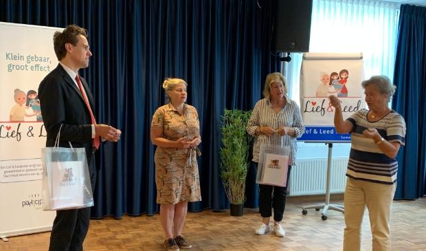 <p>Wies Drijver en Louke Redeker ontvangen voor Kruitmolen/ Amsteldijk Zuid een Lief &amp; Leedpotje van wethouder Marijn van Ballegooijen (Zorg en Welzijn) en Sandra van Engelen (raadslid CDA en initiatiefnemer van Lief &amp; Leedstraten in Amstelveen).</p>