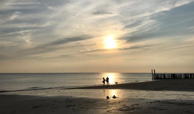 """,,Dit was op het strand Dishoek, aan het einde van een prachtige zomerdag. Toevallig liep dit verliefde stel precies in de weerkaatsing van de zon op het water. Was letterlijk en figuurlijk een geluksmomentje voor mij als fotograaf (iPhone) en dit stel."""" Klaas Hoorn © BDU Media"""