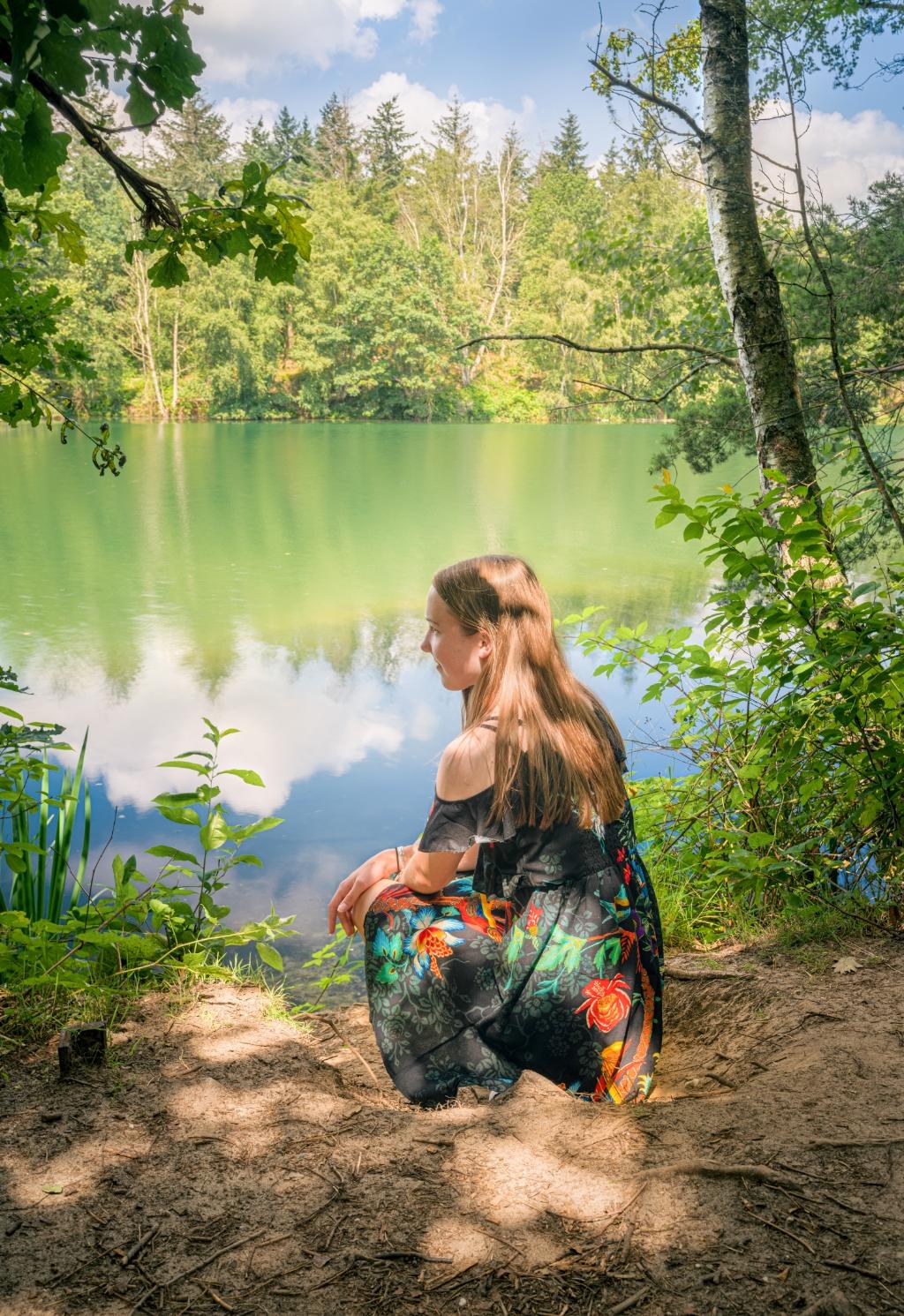 Ilse kijkt dromerig uit over het kleurrijke water van De Maasduinen. De foto is gemaakt op 22 juli 2021 in Nationaal Park De Maasduinen. Ik was daar op vakantie met mijn vriendin en schoonfamilie. Op de foto staat Ilse Bom, mijn nichtje, die zomers en kleurrijk gekleed opgaat in een zomers, kleurrijk en typisch Nederlands landschap, waar ze wegdroomt bij dit prachtige meertje.  Theo van Veenendaal © BDU media