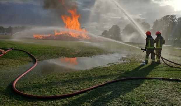 Brandweermannen houden de verbranding van Timmerdorp Gorinchem onder controle.
