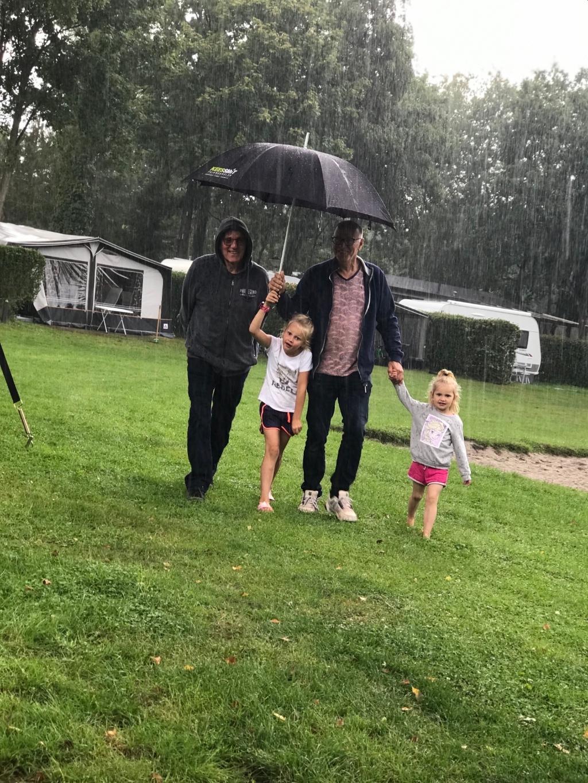 """,,Wij zijn op vakantie in Heerde. Camping de zandkuil.  Mijn ouders staan ook op de camping. Mijn vaders broer kwam op bezoek. Hij werd bij de parkeerplaats opgehaald met paraplu. Terwijl wij volwassenen ons warm kleden en droog blijven zitten in de tent, gaan de kinderen gewoon spelen. Het liefst in korte broek en blote voeten, want dat droogt t snelst op.  Onze jongste dochter van 3 jaar rende vanuit de tent dwars door de stortbui op opa af, heel blij. Die regen boeide haar niet. Het contrast tussen de kinderen en de volwassenen is hier zo duidelijk. En zeg nou eerlijk…. als de kinderen genieten, dan maakt die regen toch helemaal niks meer uit!"""" Mendi van den Broek © BDU Media"""