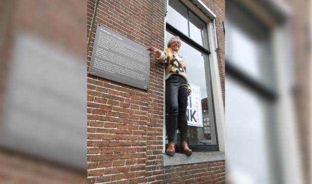 <p>Petra Boersma bij de plaquette op de gevel van Beekstraat 57, met een deel van het levensverhaal van Jo Bonger.</p>