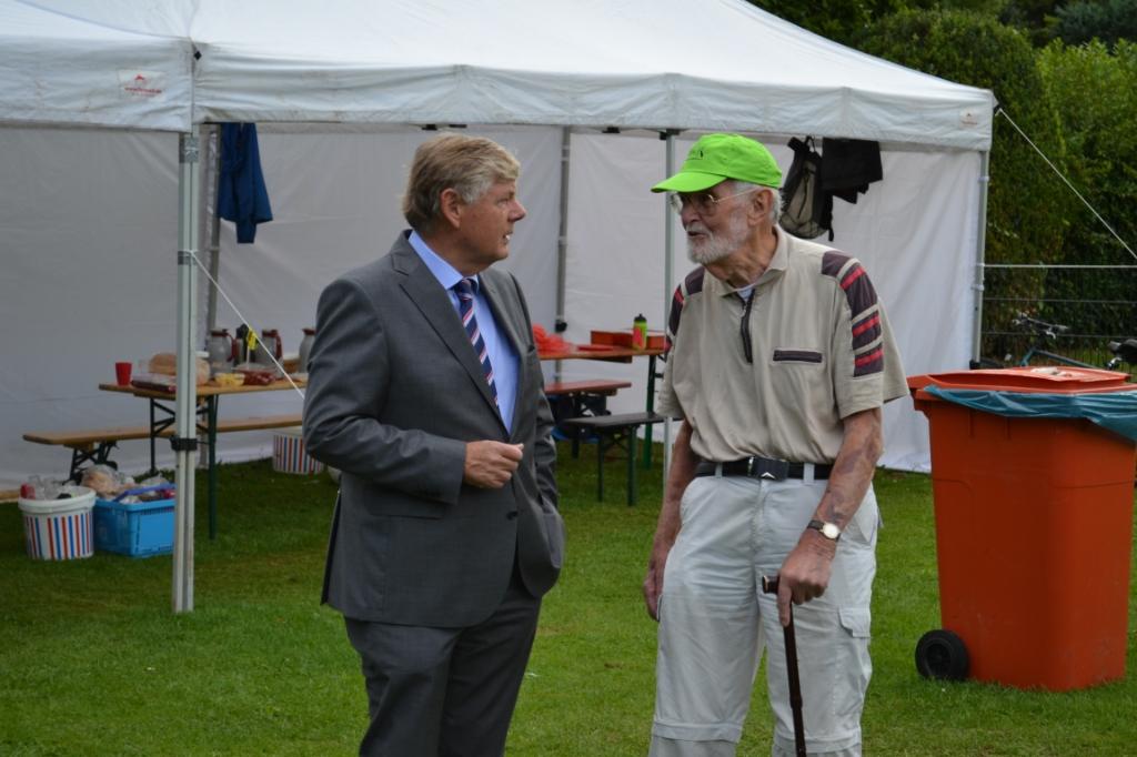 Burgemeester Roest in gesprek met Paul (89), de oudste vrijwilliger van het Huttendorp. Mariëlle Tukker © BDU Media