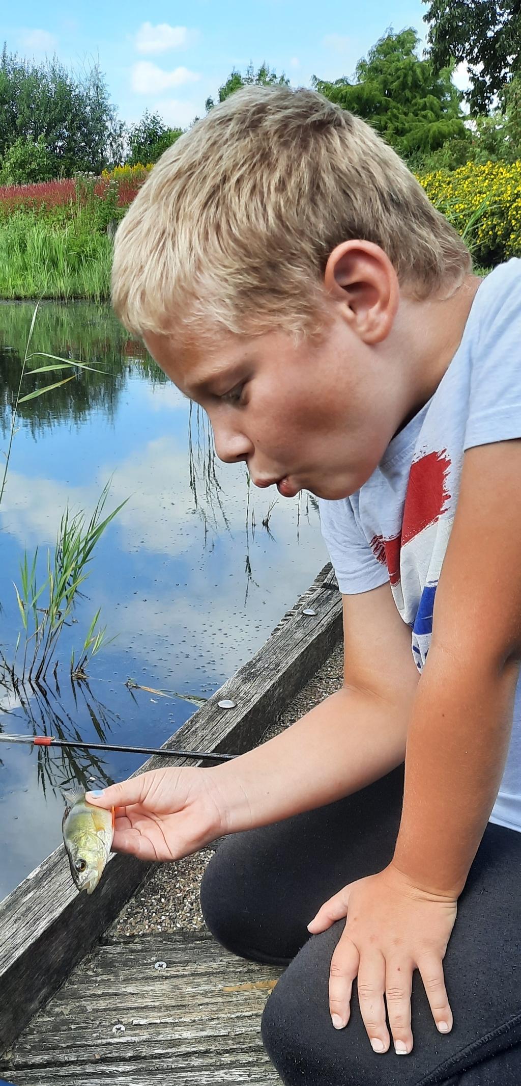 """,,Björn is een groot vis liefhebber. Op 14 augustus was het een mooie dag om samen te gaan vissen bij het Jaagpad in de wijk Corlaer. Hier een mooi baarsje gevangen.""""  Paul van der Steen © BDU Media"""