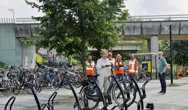 In het bijzijn van medewerkers van Prorail, de aannemer en medewerker verkeer van de gemeente plaatst wethouder Rineke Korrel haar fiets in een van de nieuwe stallingen op het Kerkplein in Duivendrecht.