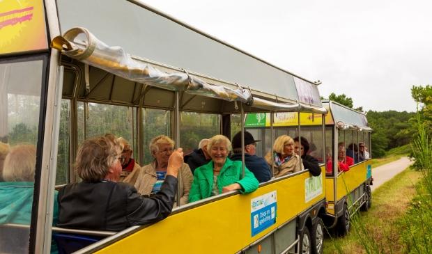 <p>Deelnemers en vrijwilligers genieten volop in het treintje in de duinen rond Schoorl</p>