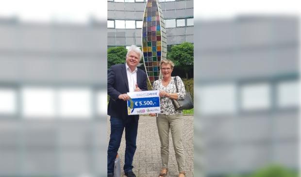 Marlene van Rooijen overhandigt de cheque aan Adriaan Theeuwes