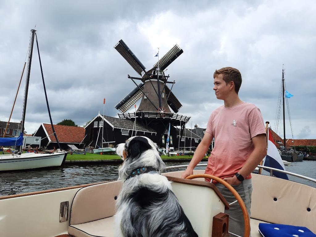 """,,Een oer Hollands plaatje. Mijn zoon Milan en onze hond Spike, varend door Woudsend. Met de Hollandse luchten, de molen, het skûtsje en de Nederlandse vlag is dit tafereel een typische foto van een vakantie in Nederland."""" Monique Verberne  © BDU"""