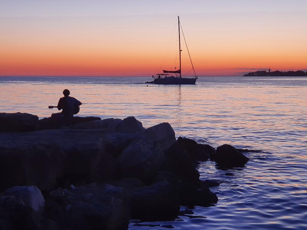 """,,Deze foto is gemaakt op woensdag 18 augustus 2021 op het strand van camping Lanterna in Kroatië, met uitzicht op Novigrad. Roy Berculo (alias Prominence) oefent zijn setlist voor het optreden van Gluren bij de buren op zondag 5 september aan de Nieuwstraat.""""  Henk Berculo © BDU Media"""