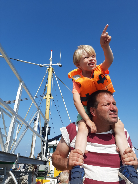 """,,Op de foto staan Yavi en zijn papa. Ze zijn op de boot op Texel. Yavi spot een zeehond in de verte."""" Shemara Houtkoop © BDU Media"""