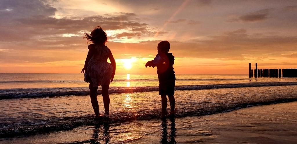 Iris (5) en Ties (3) springen bij zonsondergang in de golven in Westkapelle aan de Zeedijk, te Zeeland.  Arjan van der Zouwen © BDU