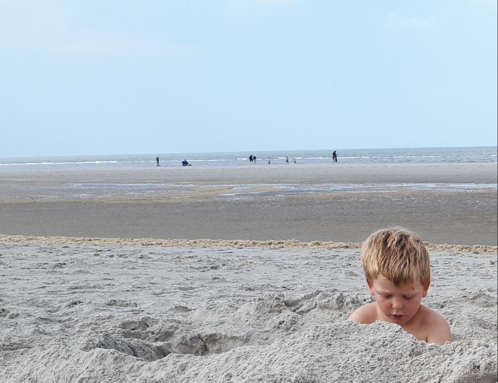 """,,Begin augustus op het strand bij Ballum (Ameland). Volop ruimte voor onze kleinzoon Lars die een week  met ons mee was. En alle tijd om een flinke kuil te graven.""""  Esse van den Burg © BDU"""