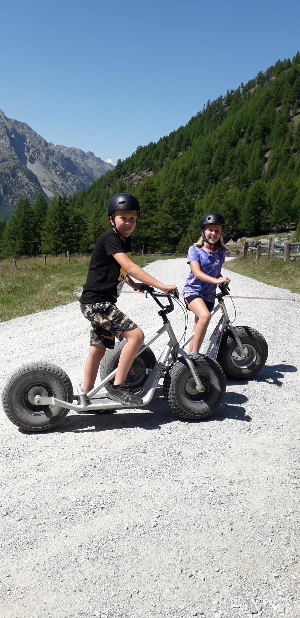 Roan en Danique in Saas-Grund (Zwitserland). Met de gondel omhoog en daarna op een step (monster-trotti) 11 km de berg weer af. Vivian 't Hart  © BDU Media