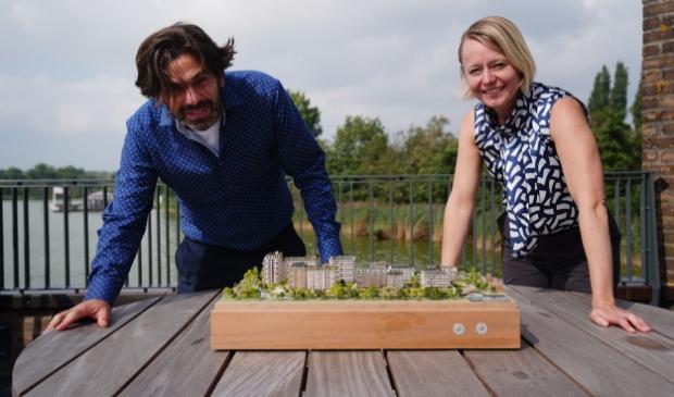 Stadsbouwer Marijn Schenk en wethouder Floor Gordon met een maquette van de wijk Olympiade.