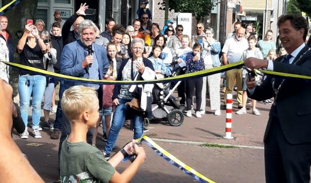 <p>Burgemeester Verhulst &#39;opent&#39; de poort, geholpen door twee basisschoolleerlingen.</p>