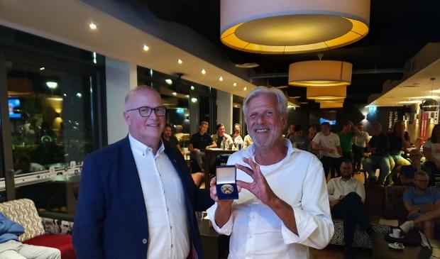 <p>Erelid Wouter Herzog (rechts) krijgt de erepenning overhandigd van zijn goede vriend en oud-voorzitter Gert van Lunteren.</p>
