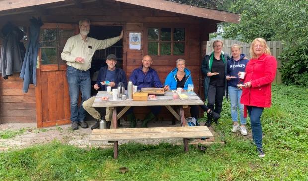 Een aantal van de vrijwilligers geniet van koffie met pruimentaart bij de nieuwe berging in de buurtboomgaard.
