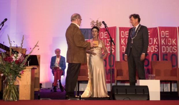 Burgemeester Verhulst krijgt een gouden doos aangereikt, met daarin het nieuwe Jubileumboek van De Kijkdoos