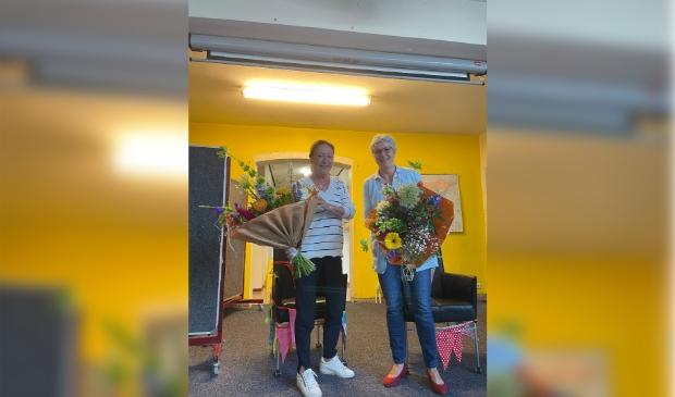 Juf Geeke (links) en juf Ria (rechts) krijgen een bos bloemen vanwege het feit dat zij 40 jaar werkzaam zijn in het onderwijs
