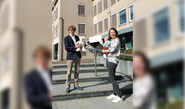 <p>Jorine Rabius ontvangt uit handen van wethouder Jan Overweg een tegoedbon voor de cursus OudersInc. De knuffelbeer is voor baby Bram. </p>
