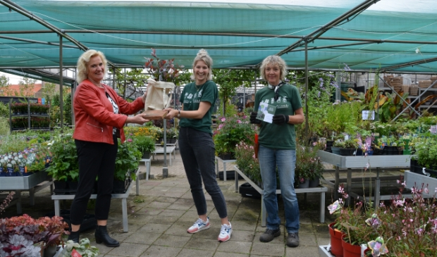 <p>Wethouder Wil Kosterman met tegel, Corienne Merkens van Merkens Tuincentrum met gratis plant in tas en Lianne Peters van Merkens. &nbsp;</p>