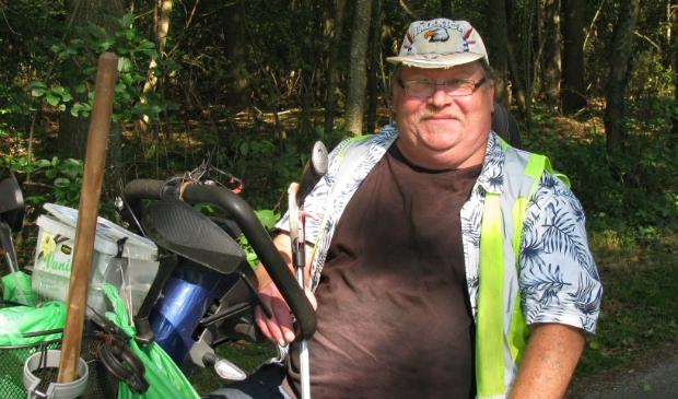 <p>Johannes Winkel op zijn scootmobiel in het groen.</p>